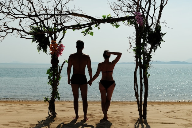 Молодая пара мужчина и женщина на обратной стороне пляжа