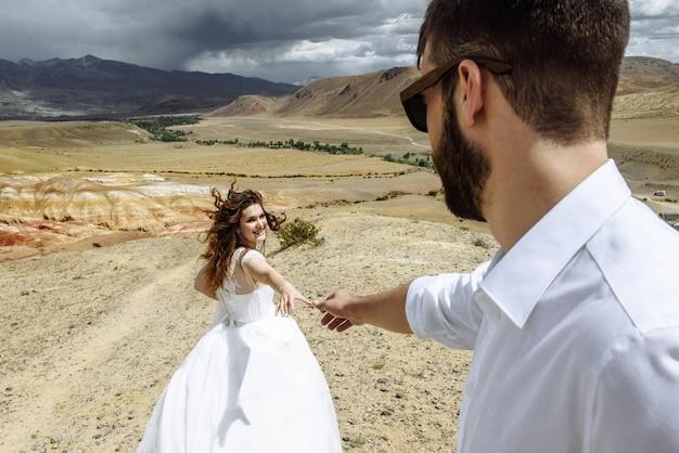 新婚夫婦の若いカップルは、結婚式の日に山の砂漠で男性と花嫁の妻を新郎します。ハネムーン旅行のコンセプト