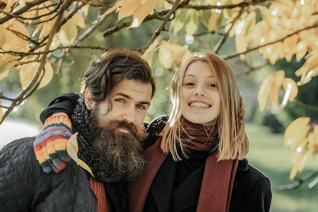 Молодая пара красивой девушки и бородатого мужчины-хипстера на открытом воздухе в осеннем парке с желтыми листьями на естественном фоне в красочных перчатках