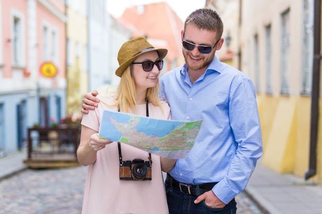 Молодая пара улыбающихся туристов, идущих с картой города