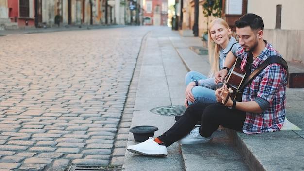 Молодая пара уличных певцов в старой части города, сидя на тротуаре. мужчина играет на гитаре и поет женщина.