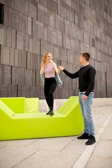 Молодая пара студентов, весело проводящих время на открытом воздухе. городская концепция.