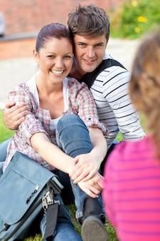 女性の友達と話す草の上に座っている学生の若いカップル
