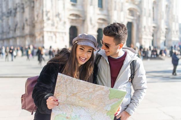 イタリア、ミラノで地図を保持している観光客の若いカップル
