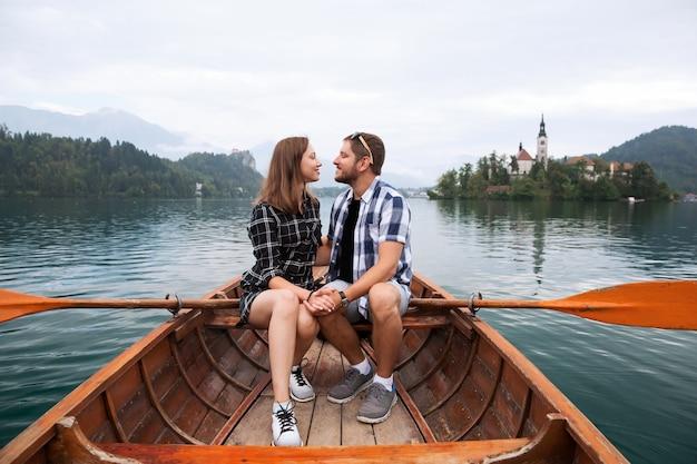 Молодая пара влюбленных туристов на традиционной деревянной лодке на озере блед словения