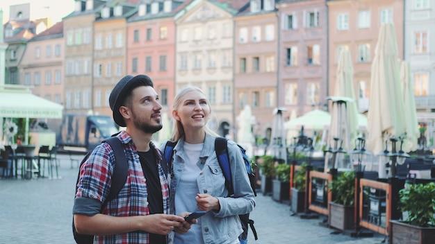 Молодая пара туристов с помощью смартфона и любуясь красивыми окрестностями. рано утром они собираются на экскурсию.
