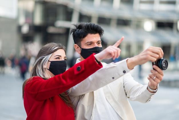 Covidまたはコロナウイルスのパンデミック中に都市で写真を撮る観光客の若いカップル