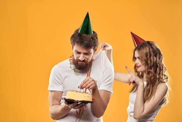 Молодая пара на день рождения с тортом и свечой в праздничных шапках