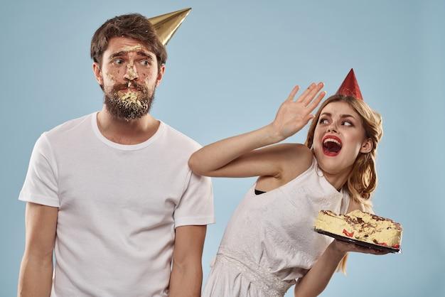 ケーキとお祝い帽子のキャンドルで誕生日に若いカップル