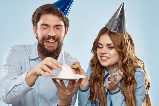 Молодая пара на день рождения с кексом и свечой в праздничных шапках