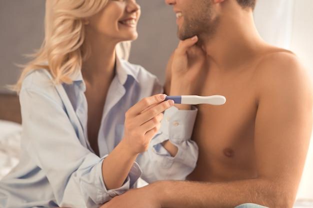 ベッドの妊娠検査チェックの若いカップル