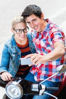 태블릿 pc를 사용하여 베스파 투어를 계획중인 베를린 시내 여행중인 젊은 커플