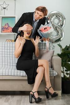 花束を持って、リビングルームで女性とソファで後ろに立っている彼女の目を覆った幸せな女性の日の男の若いカップル