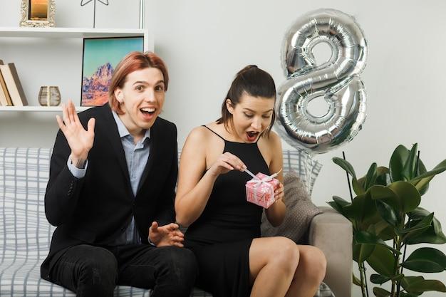 Молодая пара в счастливый женский день держит и открывает подарок, сидя на диване в гостиной