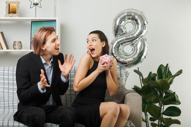 リビングルームのソファに座ってプレゼントを保持している幸せな女性の日の若いカップル