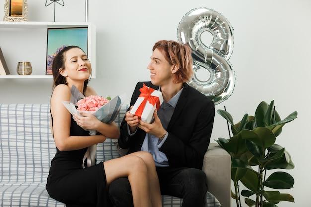 リビングルームのソファに座っている花束とプレゼントを保持している幸せな女性の日の若いカップル