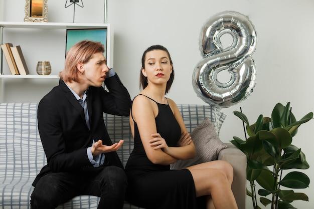 幸せな女性の日の若いカップル悲しい男は、リビングルームのソファに座っている厳格な女の子を見て手を広げます