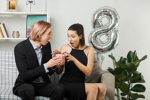 Молодая пара в счастливый женский день улыбается парень дает подарок возбужденной женщине, сидящей на диване в гостиной
