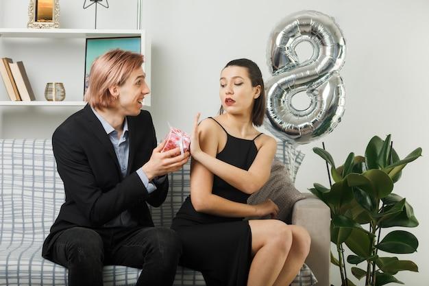 Молодая пара в счастливый женский день улыбается парень делает подарок недовольной девушке, сидящей на диване в гостиной