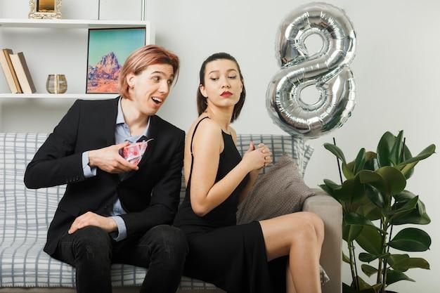 幸せな女性の日の若いカップルの笑顔の男は、リビングルームのソファに座っている不機嫌な女の子にプレゼントを贈る