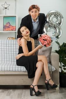 Молодая пара в счастливый женский день улыбается парень стоит за диваном грустная девушка сидит на диване с букетом в гостиной