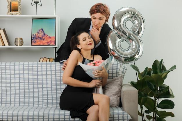 幸せな女性の日の若いカップルは、ソファの女の子の後ろに立っているあごの男をつかんで、リビングルームで花束を持ってソファに座って喜んでいると考えています