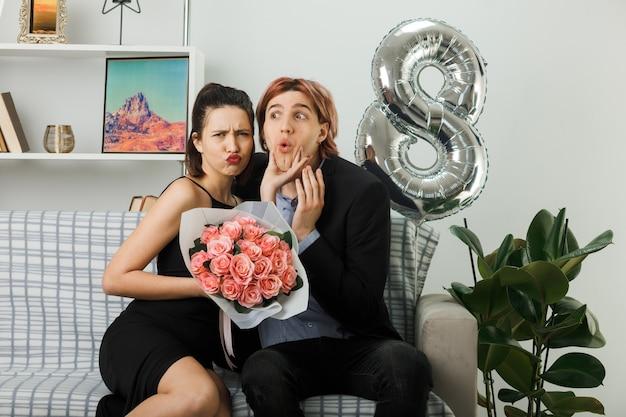 Молодая пара в счастливый женский день недовольная девушка с букетом схватилась за подбородок, сидя на диване в гостиной