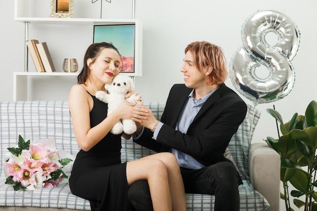 リビングルームのソファに座っているテディベアと幸せな女性の日の若いカップル