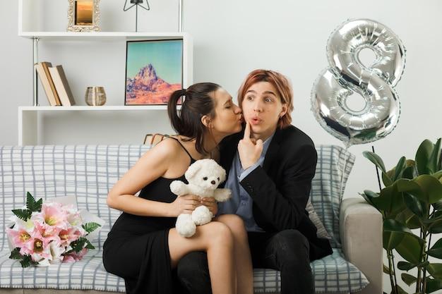 リビングルームのソファに座って彼の頬にキスするテディベアの女性と幸せな女性の日の若いカップル