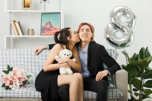 Молодая пара в счастливый женский день с женщиной-плюшевым мишкой, целующей его в щеку, сидя на диване в гостиной