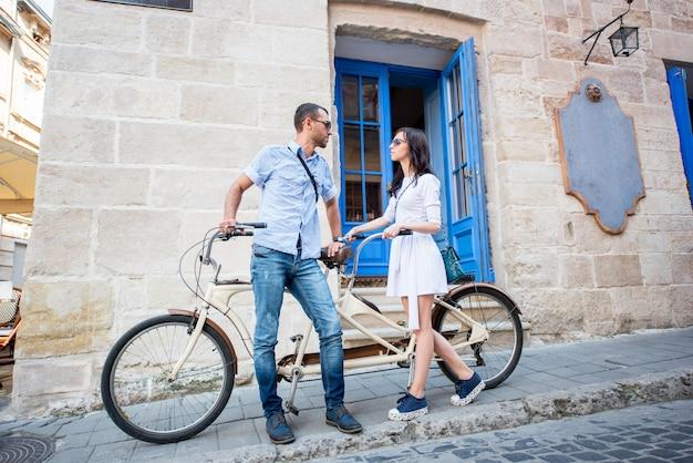 Молодая пара на тандем велосипеде на улице города