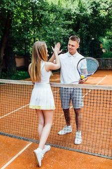テニスコートの若いカップル。ハンサムな男性と魅力的な女性は5を与える