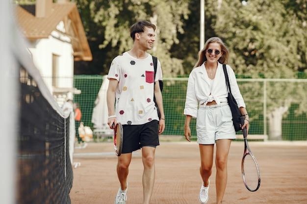 테니스 코트에 젊은 부부. 스포츠 옷에 두 테니스 선수.