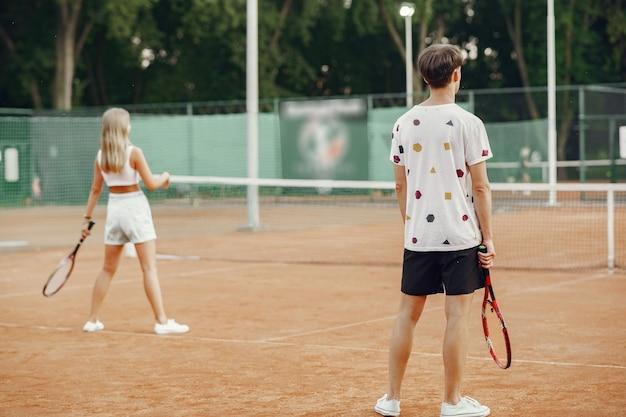 テニスコートの若いカップル。スポーツ服を着た2人のテニス選手。