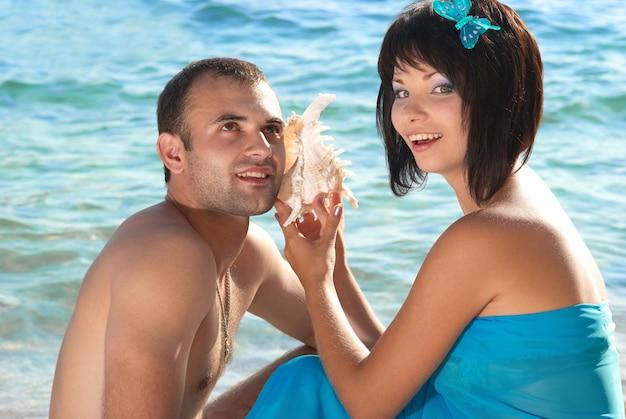 Молодая пара на пляже с ракушкой