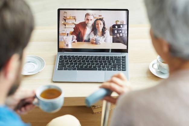 Молодая пара на мониторе ноутбука разговаривает со своей семьей онлайн дома