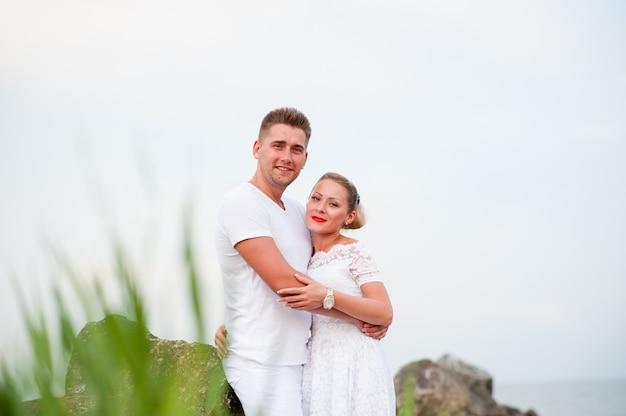 Молодая пара на скалах в море