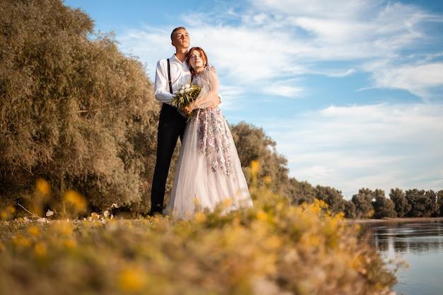 湖のほとりの結婚式の日の若いカップル