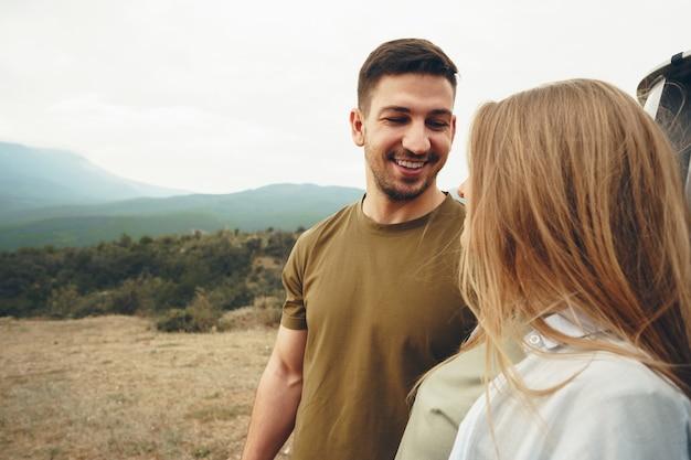 Молодая пара в поездке, расслабляясь и наслаждаясь видом на горы