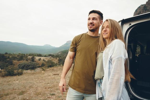 リラックスして山の景色を楽しむ旅行中の若いカップル