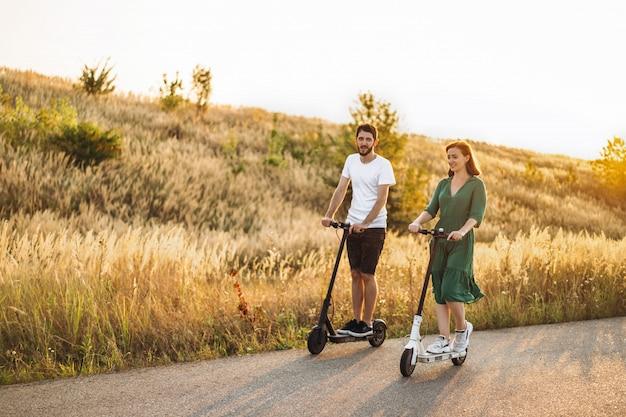 Молодая пара в отпуске весело вождения электрический скутер на дороге в сельской местности. контентные технологии. копировать пространство