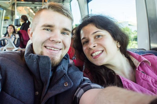 Молодая пара на отдыхе в европе на поезде фотографирует селфи.