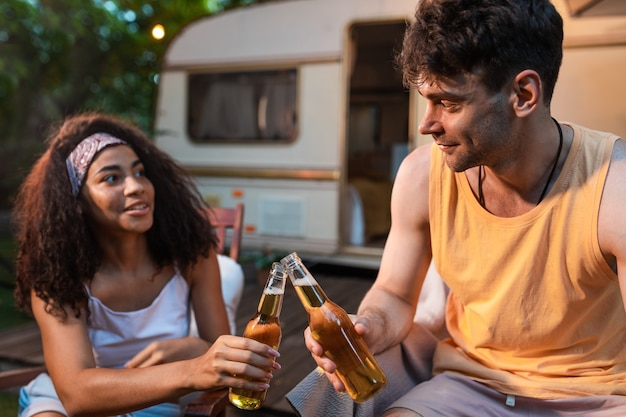 캠핑카와 함께 휴가를 보내는 젊은 부부. 오토카라반과 함께하는 여행. 방랑벽 여행과 휴가 생활 방식에 대한 개념