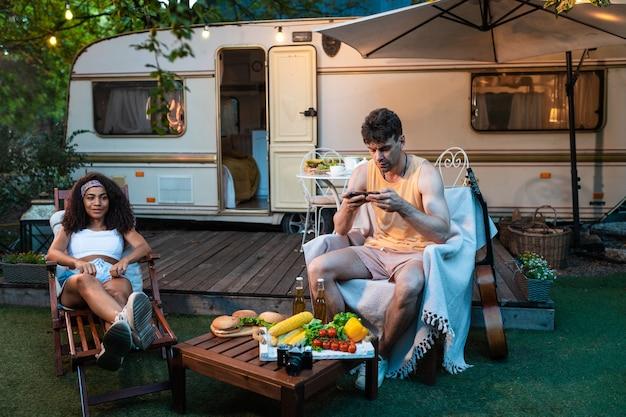 キャンピングカーと一緒に休暇中の若いカップルオートキャラバンと一緒に旅行