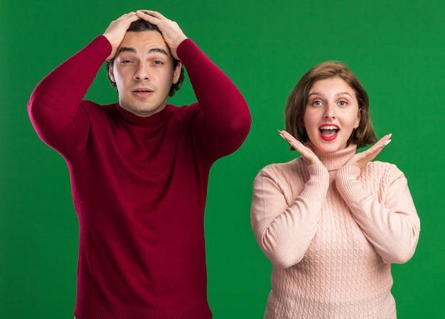 Молодая пара в день святого валентина обеспокоена мужчиной, держащим руки на голове, взволнованная женщина показывает пустые руки под подбородком и смотрит вперед, изолированную на зеленой стене