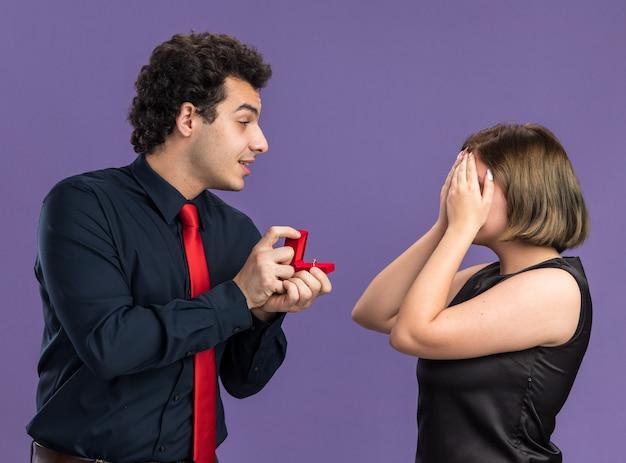 발렌타인 데이에 젊은 부부는 보라색 벽에 고립된 손으로 눈을 가린 호기심 많은 여성을 바라보는 여성에게 약혼 반지를 주는 흥분된 남자