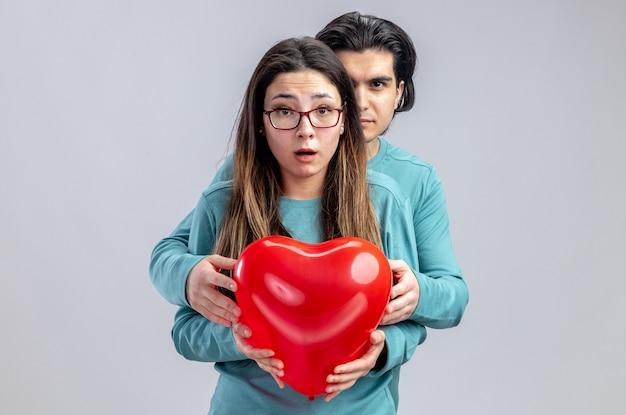 발렌타인 데이에 젊은 부부는 흰색 배경에 고립 된 심장 풍선과 함께 소녀 뒤에 서있는 자신감이 남자