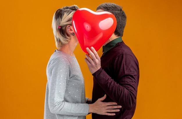 バレンタインデーの若いカップルは、オレンジ色の背景で隔離のハートの風船で顔を覆った