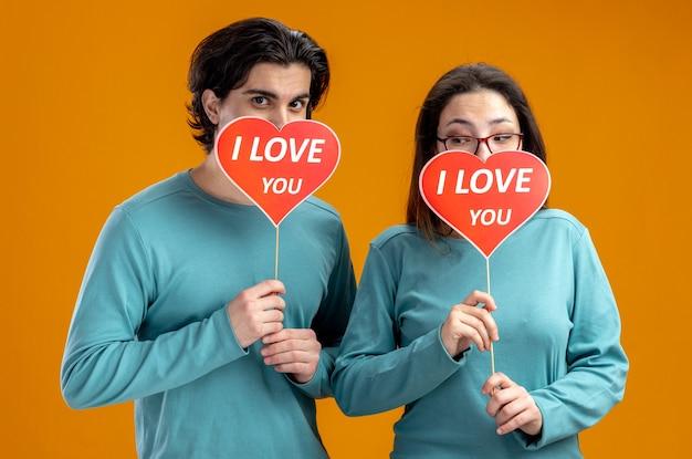 バレンタインデーの若いカップルは、オレンジ色の背景に分離されたテキストを愛して赤いハートの棒で顔を覆った
