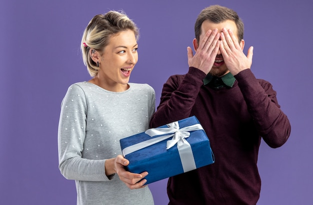 バレンタインデーの若いカップルは、青い背景で隔離の男にギフトボックスを与える興奮した女の子